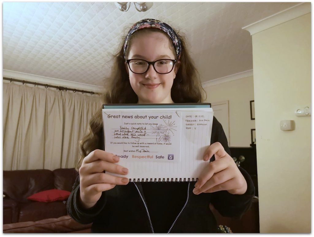 Child holding well done certificate, looking pleased and proud